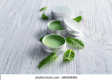 Containers with lemon balm salve and leaves on wooden table