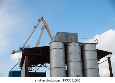 Containers and tanks on a background of blue sky. Cargo transportation. Loading sand into containers