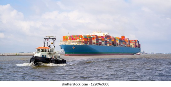 Containership and tugboat on the Elbe river near Hamburg, Germany