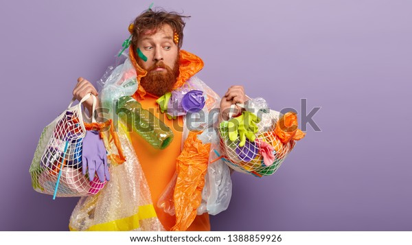 Contamination and ecological problems concept. Upset bearded red haired man holds net bags with litter, picks rubbish, cleans up environment, stands against purple background with blank space