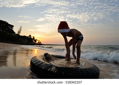 Contamination of the environment: in the rays of a sunset on the beach boy in Santa's cap playing on the automobile tires, which was thrown into the sea