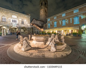 Contarini fountain on Piazza Vecchia square and Campanone tower in the old part of Bergamo, Italy at night.