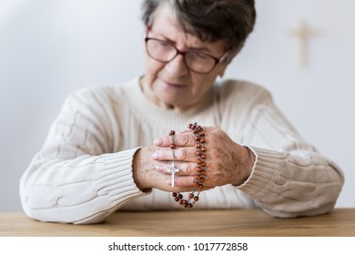 Contemplating elderly woman praying with red rosary in the church