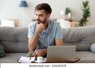 Contemplating millennial serious man looking away sitting on couch. Thoughtful pensive handsome serious male student thinking about new idea or project analysing planning making decision concept