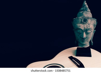 Contemplating spiritual music. Mindful songwriting. Meaningful melody. Buddha and acoustic guitar against black background with copy-space. Enlightenment and spirituality in creative song writing.