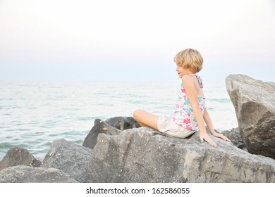 Contemplating summer while sitting on the lake side rocks, as dusk sets in at the lake, life of a young, blonde short haired girl at Centennial Park, Hamilton, Ontario, Canada.