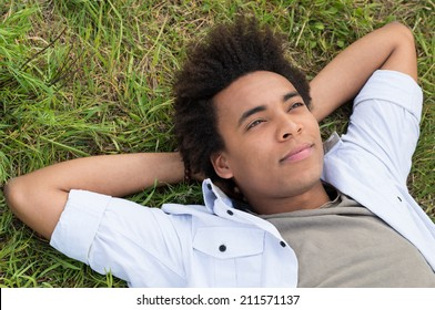 Contemplating Young African Man Lying On Grass