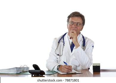 Contemplative aged doctor at desk writes prescription.Isolated on white background.