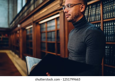 Contemplative caucasian male writer in stylish optical spectacles for provide eyes protection holding literature book in hands and looking away near bookshelf, concept of knowledge and education
