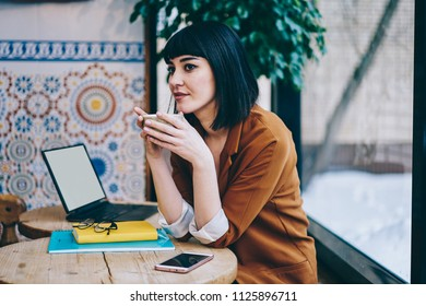 Contemplative hipster girl enjoying cup with hot tea sitting at table with mockup laptop device, pondering brunette woman dreaming about rest and holidays while waiting friend at cozy cafeteria