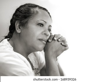 Contemplative Hispanic Woman against a light background in monochrome