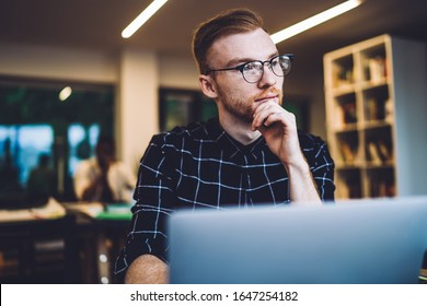 Contemplative male graphic designer pondering on medial content for downloading from web photostocks during remote work with website, pensive Caucasian man in spectacles feeling thoughtful indoors