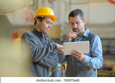 contemplative manual workers looking at digital tablet