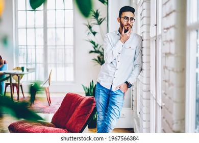Contemplative millennial hipster guy in optical eyewear for vision protection feeling pondering in loft apartment, pensive male thoughtful looking away and thinking about weekend spending in home