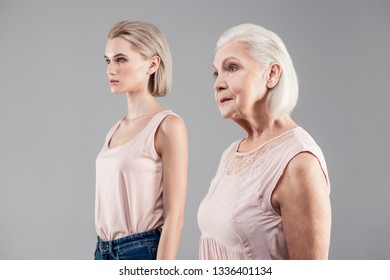 Contemplative senior. Short-haired women of different ages showing themselves from side while having grey background