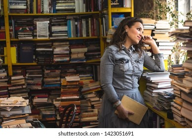 Contemplative woman among books in the bookstore or library, looking through the window, thinking or reflecting
