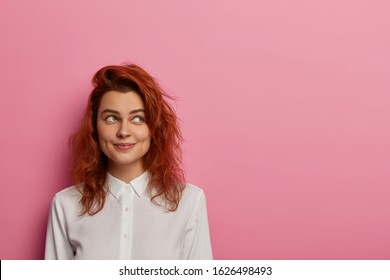 Contemplative woman with happy dreamy expression, concentrated aside, thinks about vacation after work, dressed in elegant white shirt, has ginger hair, poses against pink backgroun, makes up idea