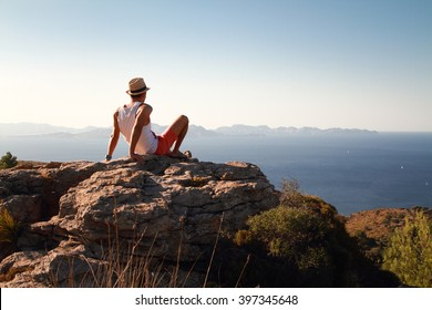 Contemplative young man sitting on the rocks on the top of the mountain at sunset. Looking at distance with the blue sea in front. Wearing a straw at in summer.