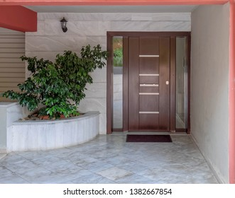 contemporary apartment building entrance covered with white marble, potted plants and dark wood door