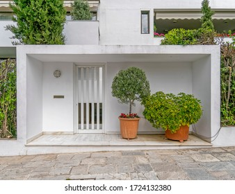 contemporary apartment building external white entrance door with potted plants
