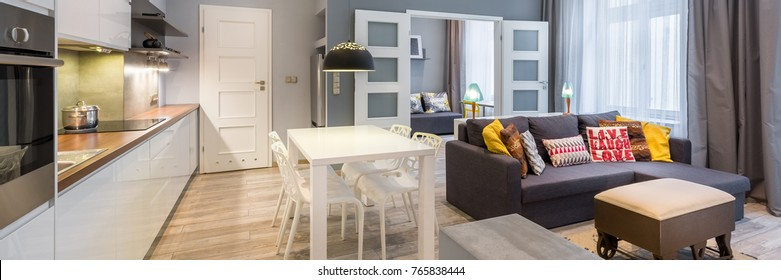 Contemporary apartment with dining table, open kitchen and living room, panorama