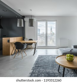 Contemporary apartment in gray with balcony, wooden table and black chairs