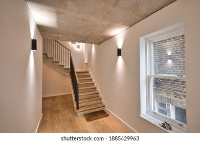 Contemporary Apartment interior design with concrete ceiling and wood flooring stairs London UK