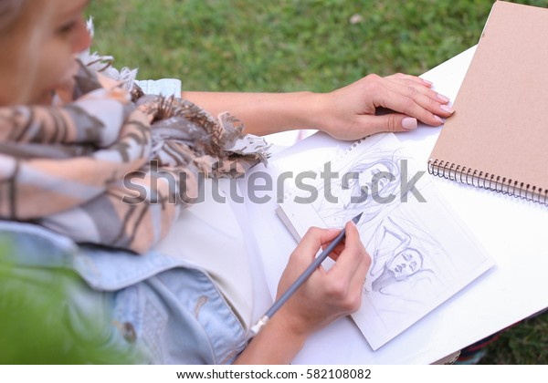 Contemporary Artist Works on Facial Contour of Depicted on Portrait Unknown Girl, Draws Sketch of Fictional Head, Prepares Gift For Friend. Woman Located in Park Outdoors in Background Stands Bench