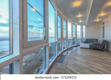 Contemporary balcony with panoramic windows and fabulous view. Hardwood floor. White ceiling. Luxury apartment with expensive designer materials.