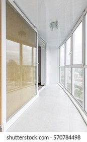 Contemporary balcony with pocket door and panoramic windows in a luxurious apartment.