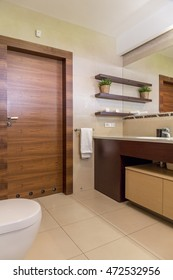 Contemporary bathroom in beige, with wooden door and tiled floor