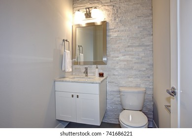Contemporary bathroom features stone accent wall framing a white bathroom vanity under a silver beveled mirror illuminated by double sconces.