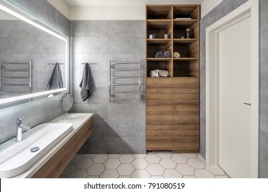 Contemporary bathroom with gray and white tiles. There is large mirror with luminous lamps, tabletop with wooden drawers and sink, towel rack and hanger, wooden locker with shelves with towels, door.