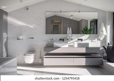 Contemporary bathroom with light walls, triangular ceiling and tiled floor. There is white bath, gray stand with two sinks, wide mirror, toilet, hanging towels, window. Sunlight falls onto them.