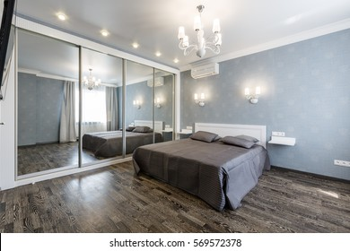 Contemporary bedroom design in a luxurious apartment. Hardwood floor, painted blue walls, white chandelier, rolling door wardrobe with mirrors.
