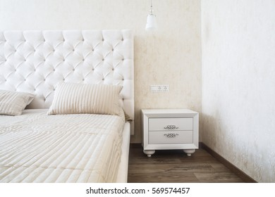 Contemporary bedroom design in a luxurious apartment. Hardwood floor, painted beige walls, white chandelier, white bed linen, white wooden furniture.