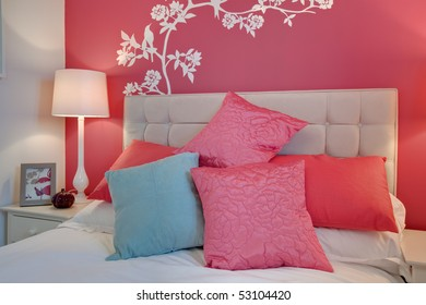 Contemporary bedroom detail with brightly colored cushions and striking pink wall mural