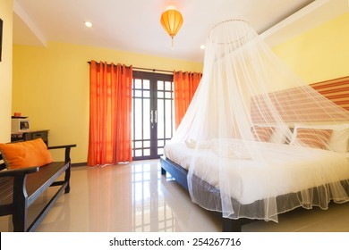 Contemporary bedroom with mosquito netting at Banana Garden Beach, Koh lanta, Krabi, Thailand.
