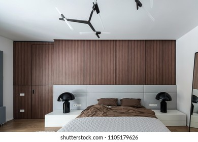 Contemporary bedroom with white walls and a parquet on the floor. There is a bed with a brown linens and a gray plaid, mirror, black lamps on stands, wooden lockers, fancy ceiling lamps. Horizontal.