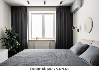 Contemporary bedroom with white walls with a relief picture. There is a double bed with gray linens and pillows, black hanging lamp, window with dark curtains, clock, green plant in the pot, stand.