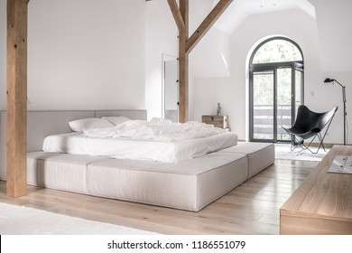 Contemporary bedroom with white walls, wooden beams and a parquet with carpets. There is a gray bed with light linens, doors to a balcony, black armchair and a lamp, chests with a statuette, stand.