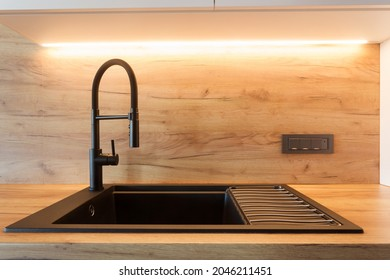 Contemporary black faucet with the lever. New spigot at kitchen