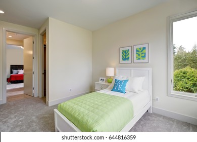 Contemporary blue and green kid's bedroom with walls painted cream and grey carpet floor. Northwest, USA.