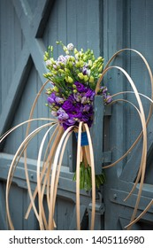 contemporary bouquet with various purple lisianthus flowers on a blue barn door