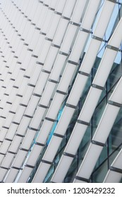 Contemporary building façade with white slats over glass, that reflects the sky