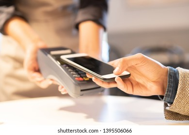 Contemporary businessman using system of contactless payment in smartphone while paying for order in cafe or restaurant