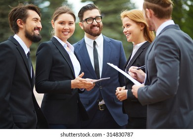 Contemporary businesswoman with touchpad looking at camera during outdoor meeting with partners