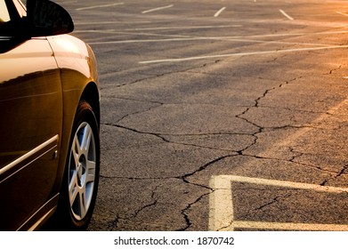 A contemporary car at sunset in an empty parking lot.