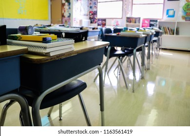 Contemporary classroom interior with lined desks complete with untouched student supplies sitting atop the wooden surface