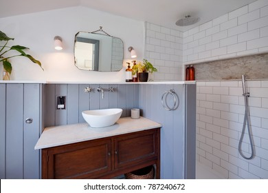 Contemporary compact wet room with traditional twist including washstand, basin with fawcet above, marble top, wood panelled and tiled walls, mirror and wall lights